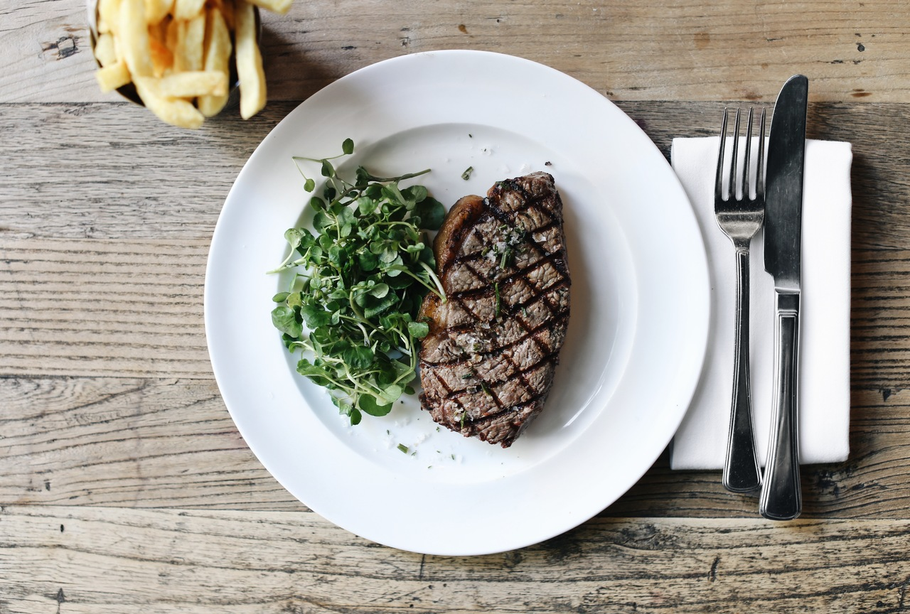 Dish of sirloin steak with spinach and chips