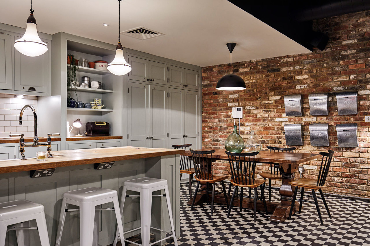 A dining table and chairs by an exposed brick wall